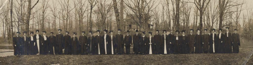 The graduating class of 1909 in black caps and gowns standing in a single file on the campus grounds.