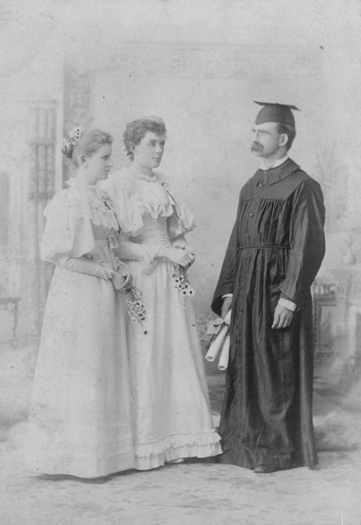 Two women students stand with President Slocum in his black graduation cap and gown holding two diplomas.