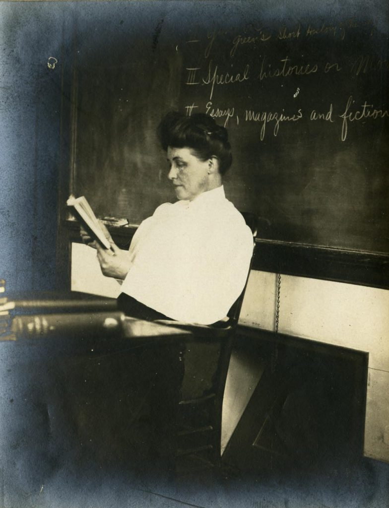 "Miss Ella Fulton sits at her desk reading a book. The chalkboard behind her has ""Special histories"" and ""Essays, magazines or fiction"" written on it."