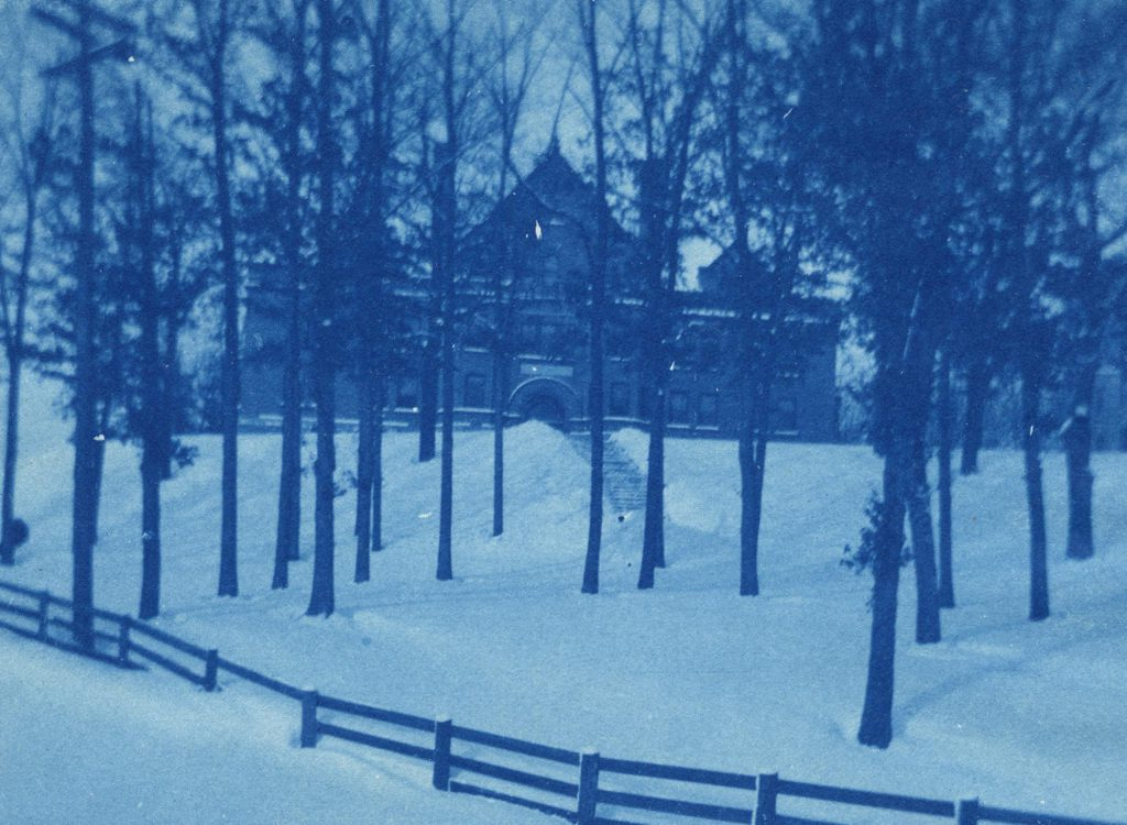 A cyanotype image of the classroom building Bowen Hall on top of a snow-covered hill lined with trees and enclosed by a fence.