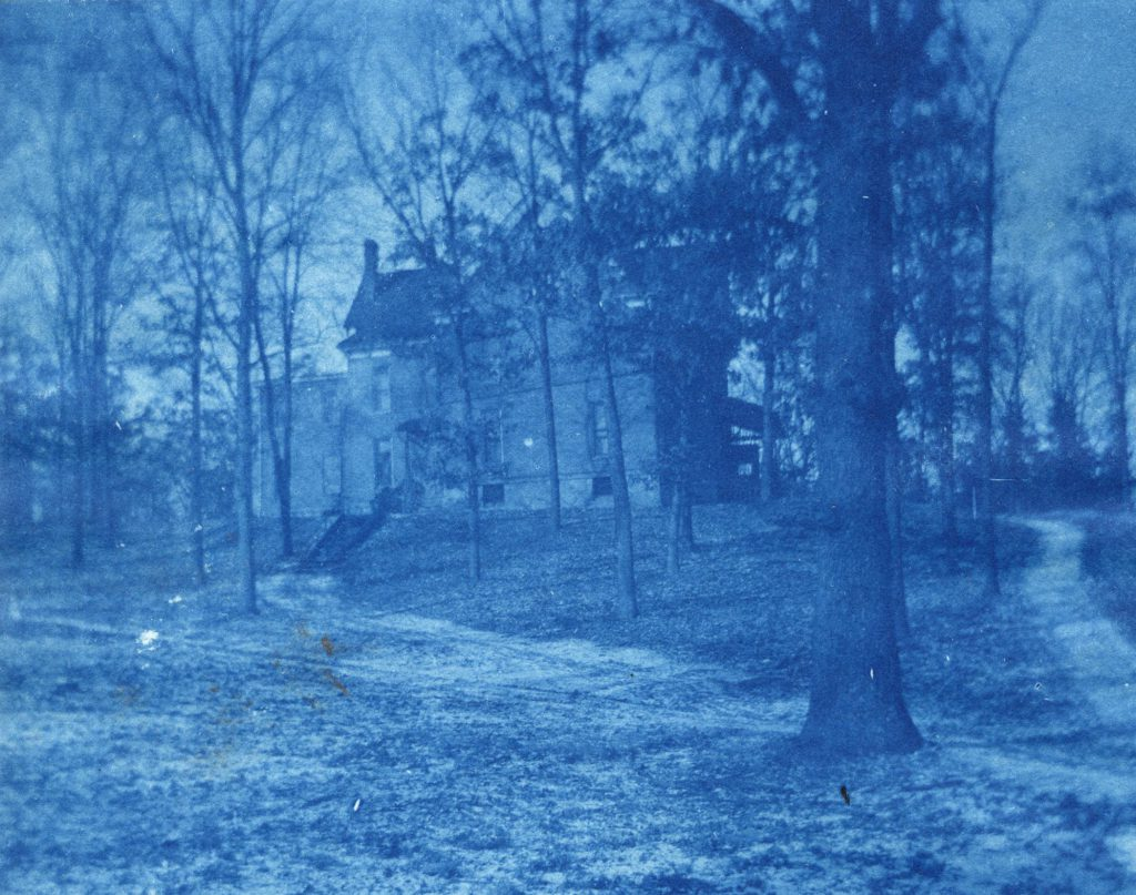 A cyanotype image of Ladies' Hall on top of a tree covered hill.