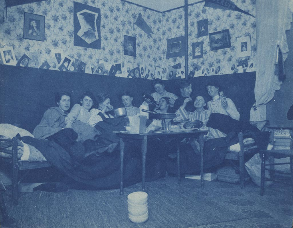 A cyanotype image of nine women students sit on trundle beds in a student's room in Ladies' Hall enjoying a spread of what is most likely fudge.