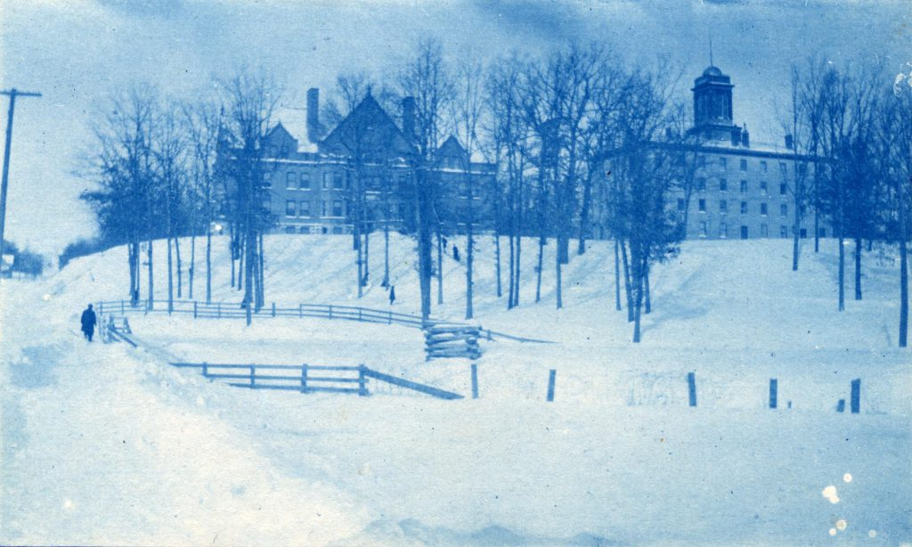 A cyanotype image of Bowen and Upper Halls atop a snow-covered hill with bare trees. A man walks alongside a fence at the bottom of the hill.