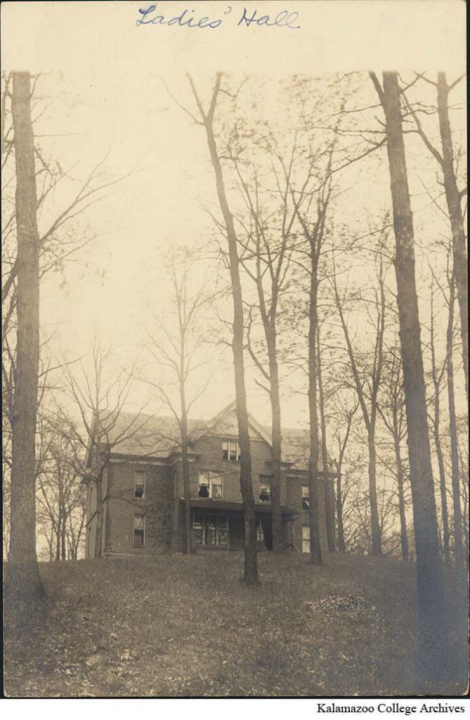 Ladies' Hall, a large red brick house, stands atop a hill covered in bare trees.