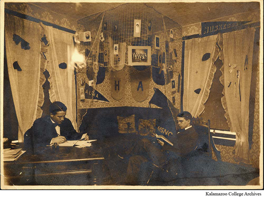 Two male students studying in their dorm room decorated with photographs hanging from netting and a pennants on the wall.