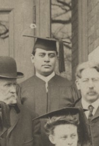 Charles Lewis Williams stands in his black graduation cap and gown on the steps of Bowen Hall.