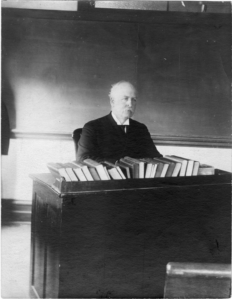 George Abner Williams sits behind his classroom desk which is covered in books.