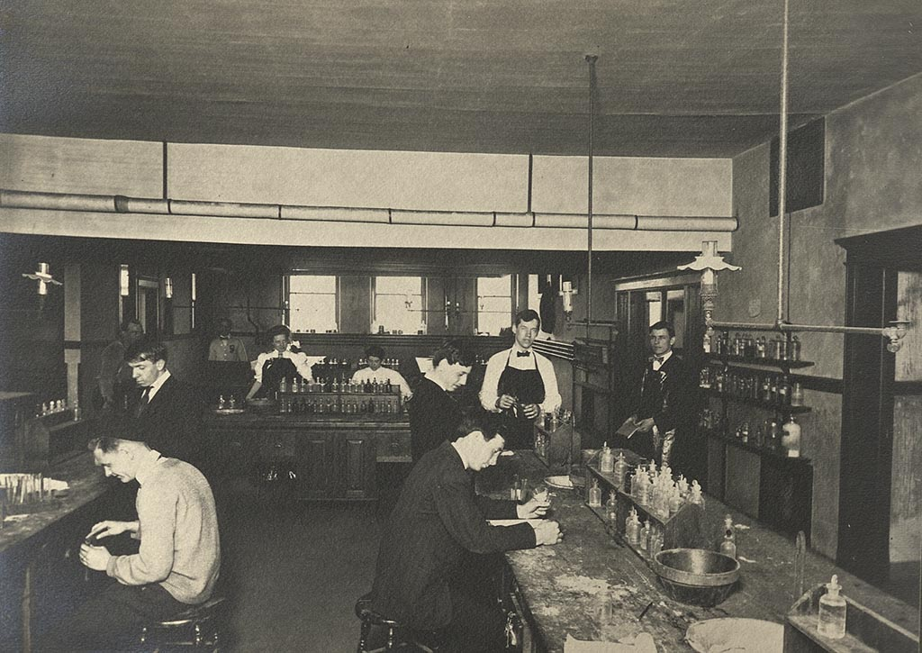 Students, some sitting and some standing, work at lab tables with glass jars of chemicals in a Bowen Hall laboratory.
