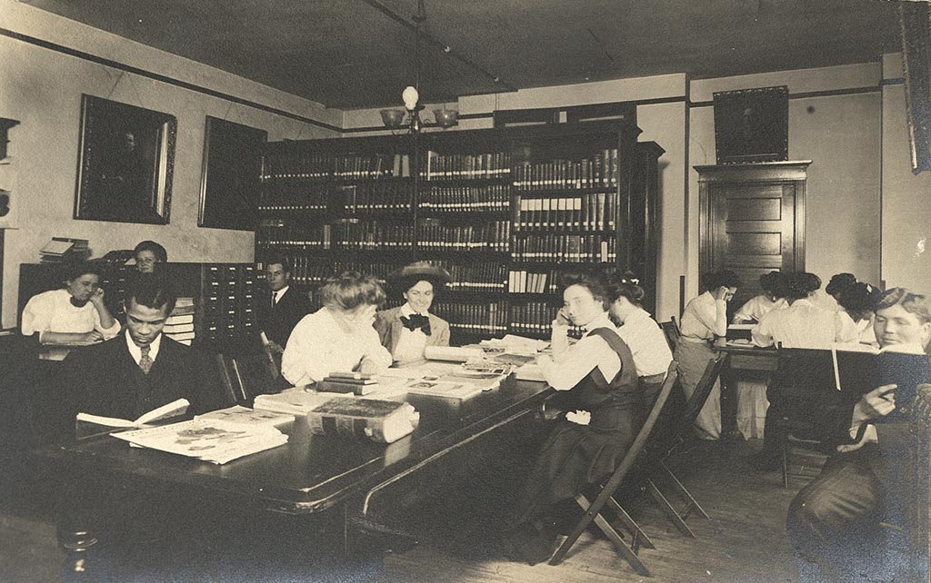 Male and female students sit at tables in front of library shelves reading books in the library.