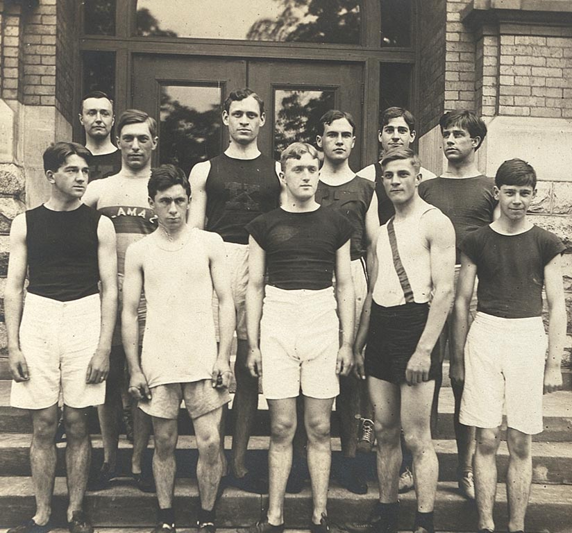 Eleven men from the track and field team, dressed in track shorts and shirts, stand on the steps of Bowen Hall.