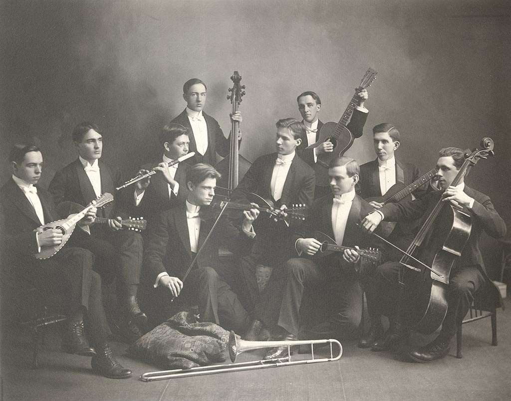 10 men from the Glee and Mandolin Club dressed in black suits and white bow ties each holding an instrument.