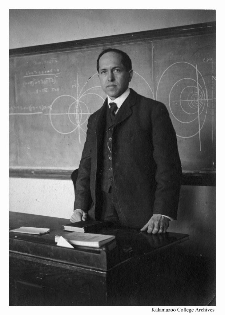 Clark Benedict Williams in a suit and tie stands behind his desk in front of the blackboard.
